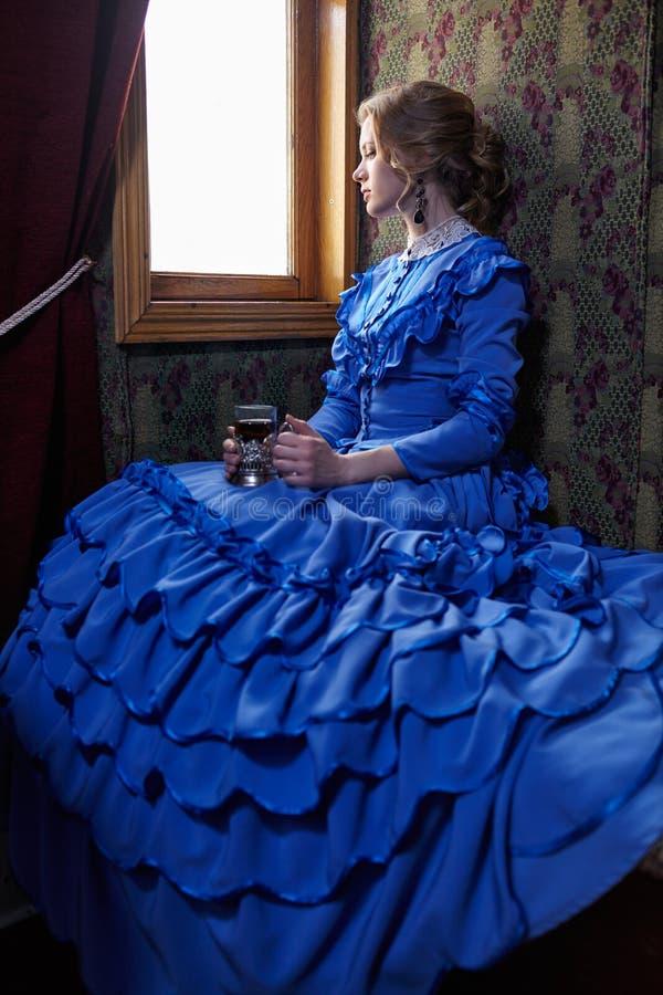Młoda kobieta w błękitnym rocznik sukni obsiadaniu w coupe retro raja fotografia stock