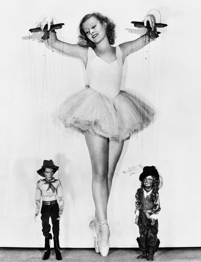 Młoda kobieta w baleriny spódniczki baletnicy utrzymaniach na jej palec u nogi kontrolować mężczyzna przy jej ciekami (Wszystkie  obraz royalty free