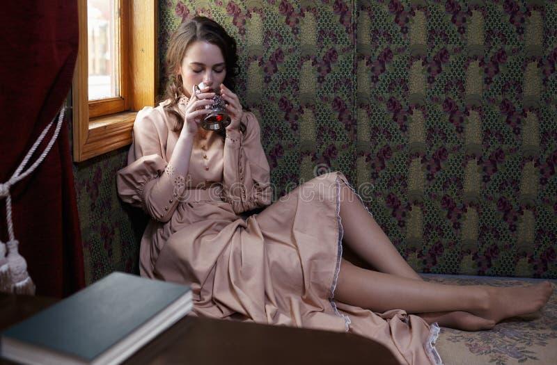 Młoda kobieta w beżowej rocznik sukni początek 20 wieku wieka drinkin zdjęcia stock