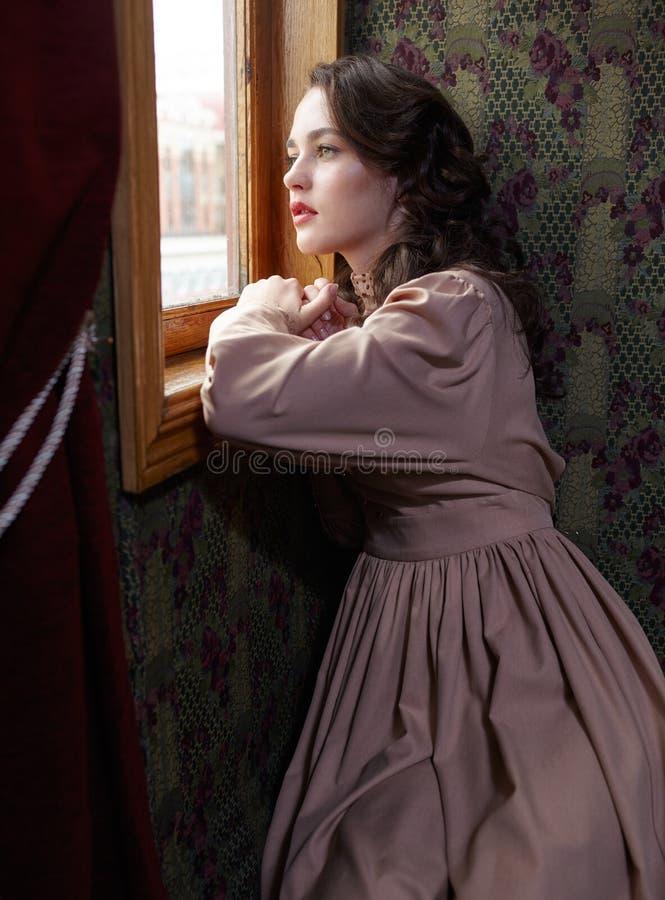 Młoda kobieta w beżowej rocznik sukni przyglądającej synklinie okno wewnątrz obraz stock