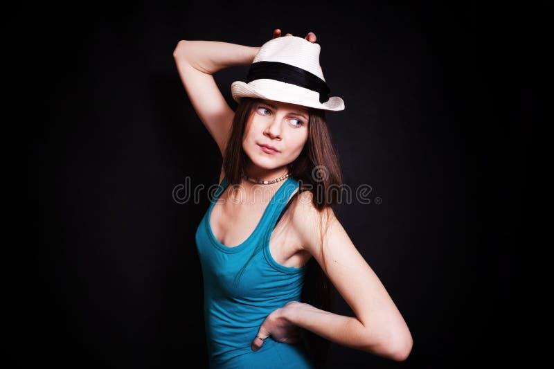 Młoda kobieta w biały kapeluszu na czarny tle obrazy stock