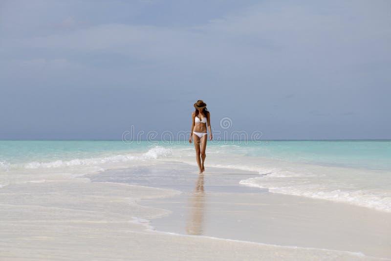 Młoda kobieta w białym bikini odprowadzeniu na plaży zdjęcia royalty free
