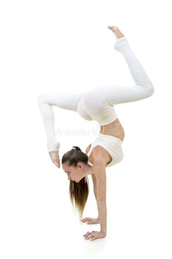 Młoda kobieta w białym kostiumu wykonuje akrobatycznych elementy i joga obraz stock
