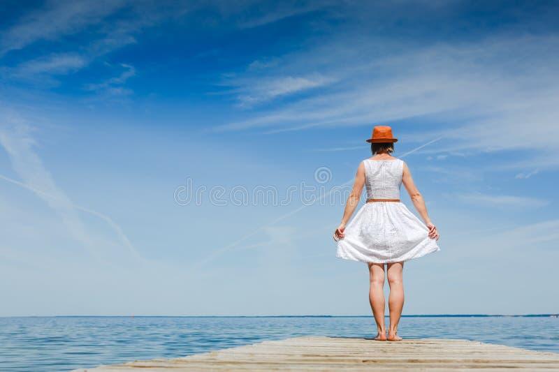 Młoda kobieta w bielu smokingowy sunbathing przy nadmorski obrazy stock
