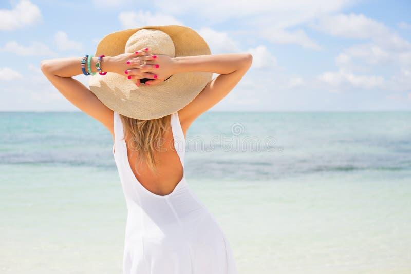 Młoda kobieta w bielu smokingowym i słomianym kapeluszu na plaży zdjęcie royalty free