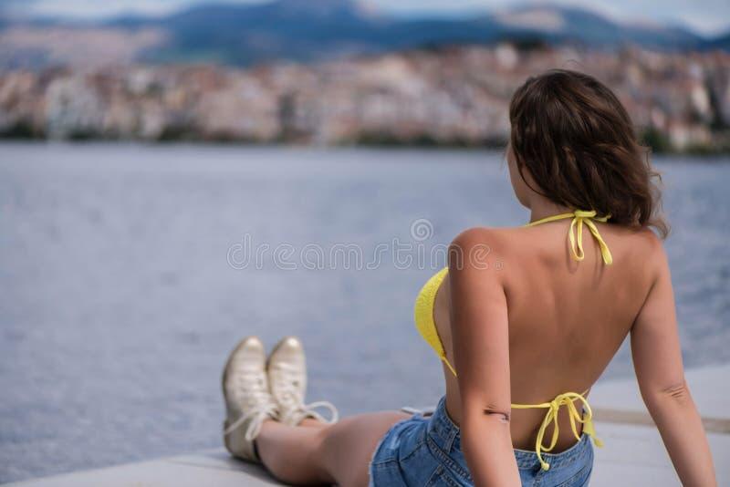 Młoda kobieta w bikini na drewnianym moscie na Kastoria miasteczku Orestias jeziora tle i Grecja zdjęcia royalty free