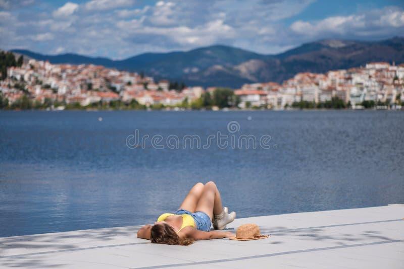 Młoda kobieta w bikini na drewnianym moscie na Kastoria miasteczku Orestias jeziora tle i Grecja obraz royalty free