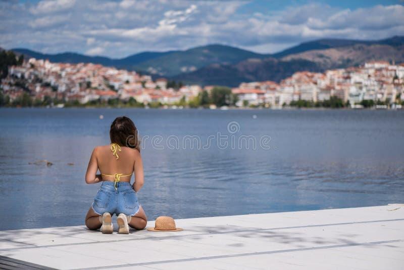Młoda kobieta w bikini na drewnianym moscie na Kastoria miasteczku Orestias jeziora tle i Grecja zdjęcie stock