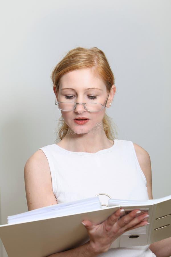 Młoda kobieta w biurowym spojrzeniu w ich kartoteki zdjęcia royalty free