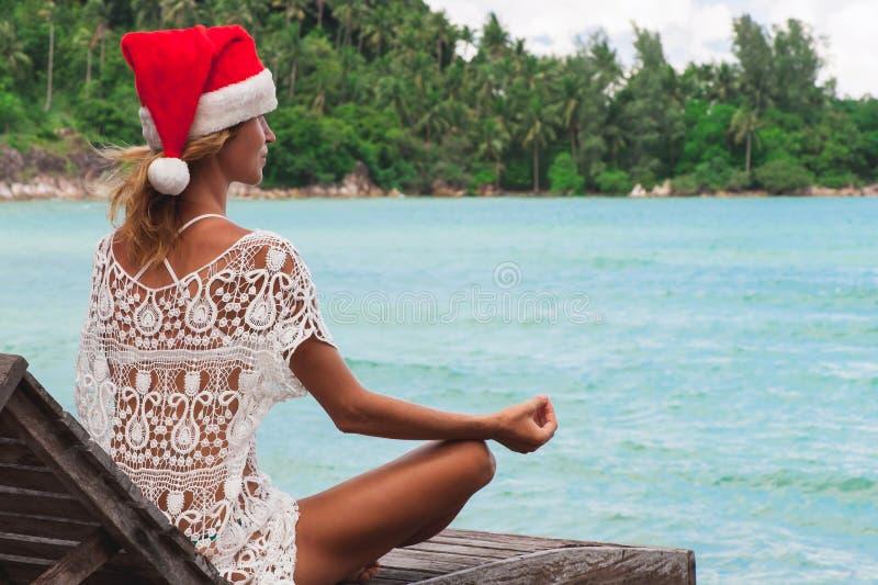 Młoda kobieta w boże narodzenie kapeluszu medytuje w joga pozie zdjęcia stock