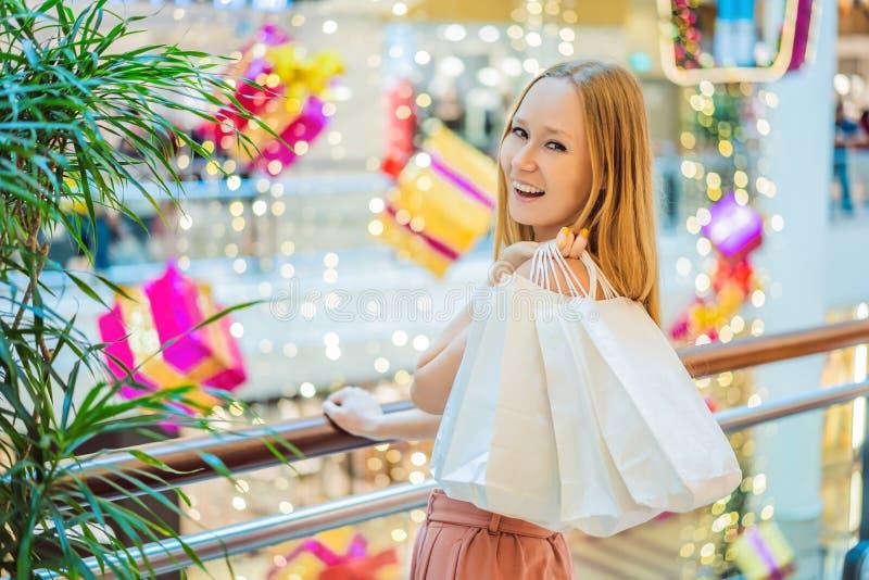 Młoda kobieta w Bożenarodzeniowym centrum handlowym z Bożenarodzeniowym zakupy Piękno bu obraz stock