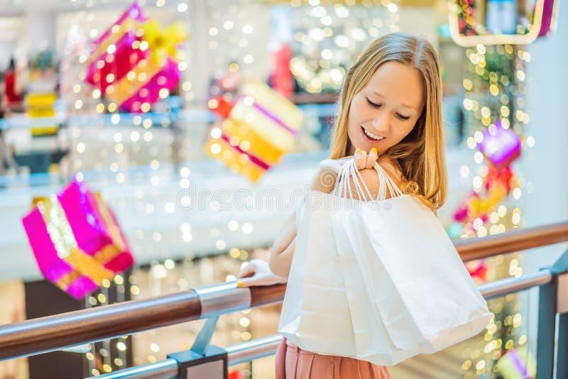 Młoda kobieta w Bożenarodzeniowym centrum handlowym z Bożenarodzeniowym zakupy Piękno bu zdjęcie stock