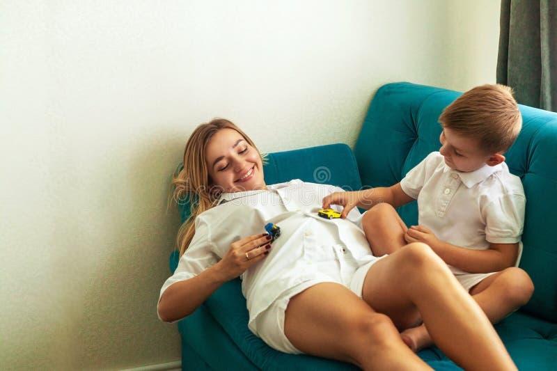 Młoda kobieta w ciąży, bawić się z chłopiec, przytuleniem i śmiać się jej, fotografia royalty free