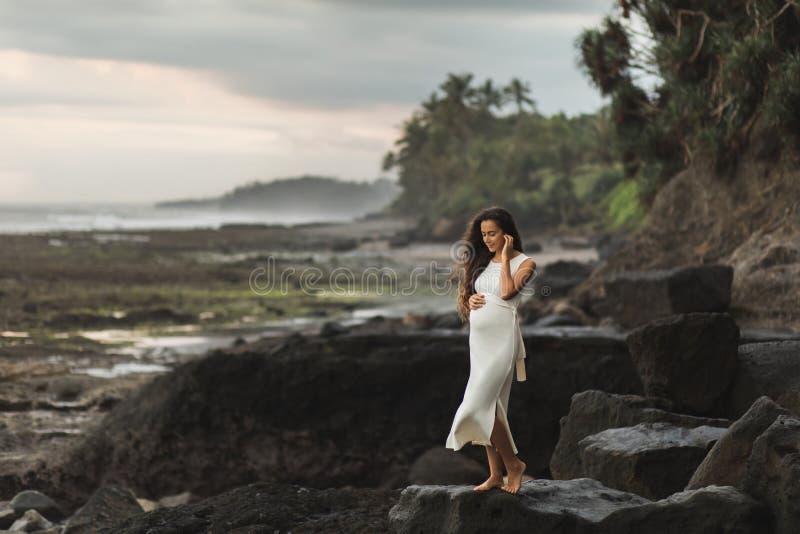 Młoda kobieta w ciąży w biel sukni na kamień plaży zdjęcia stock
