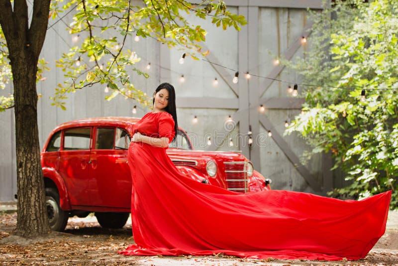 Młoda kobieta w ciąży w jesień ogródzie blisko czerwonego retro samochodu zdjęcia royalty free