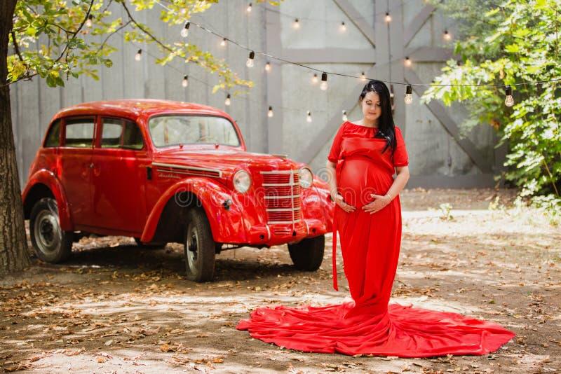 Młoda kobieta w ciąży w jesień ogródzie blisko czerwonego retro samochodu fotografia stock