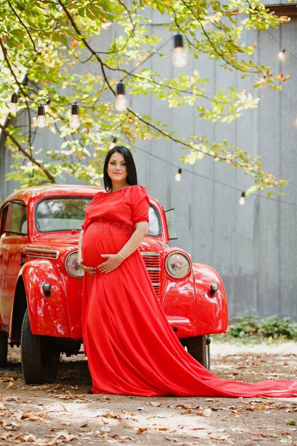 Młoda kobieta w ciąży w jesień ogródzie blisko czerwonego retro samochodu zdjęcie royalty free