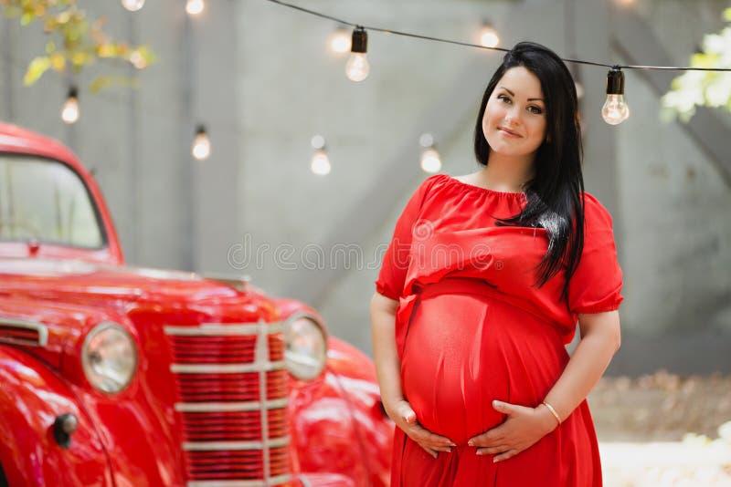 Młoda kobieta w ciąży w jesień ogródzie zdjęcia stock