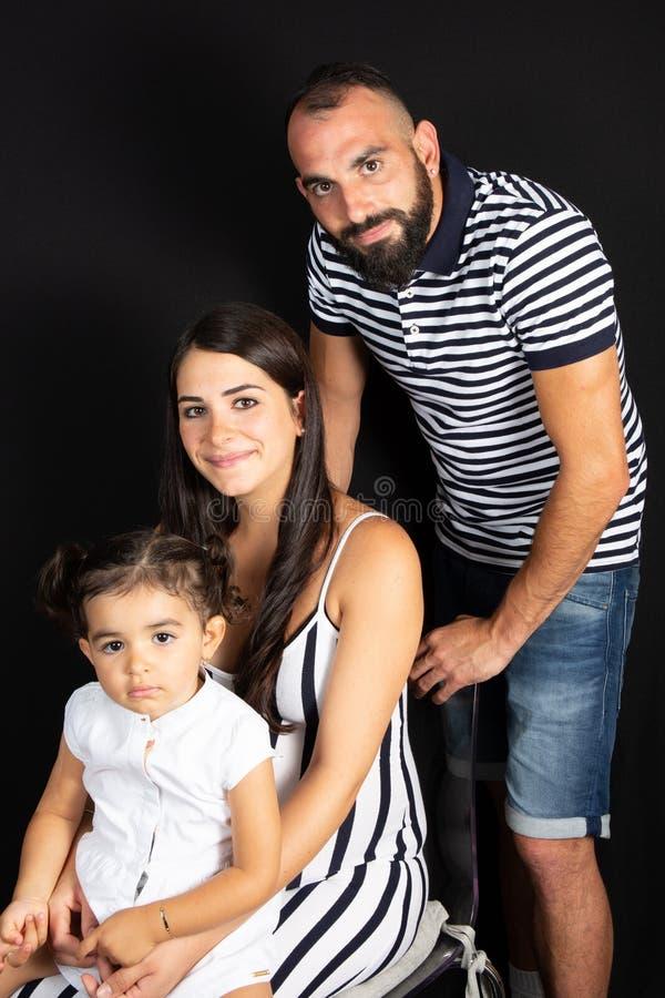 Młoda kobieta w ciąży z jej córką na czarnym tle i domatorem obraz stock