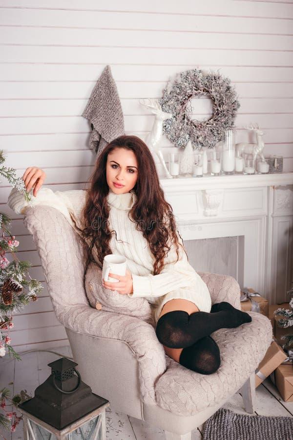Młoda kobieta w ciepłym pulowerze, trzymający filiżanki i napoju gorącej herbaty, obraz royalty free