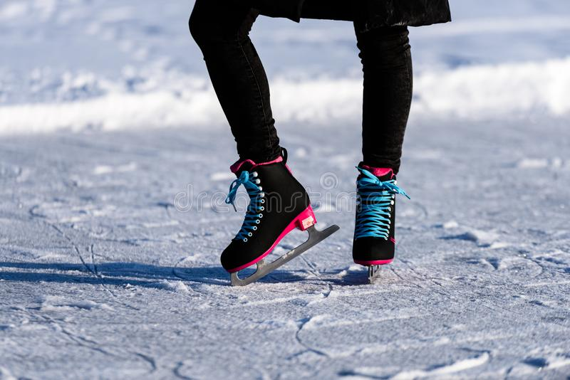 młoda kobieta w czarnym żakieta łyżwiarstwie na zamarzniętym jeziorze w śniegu obraz stock