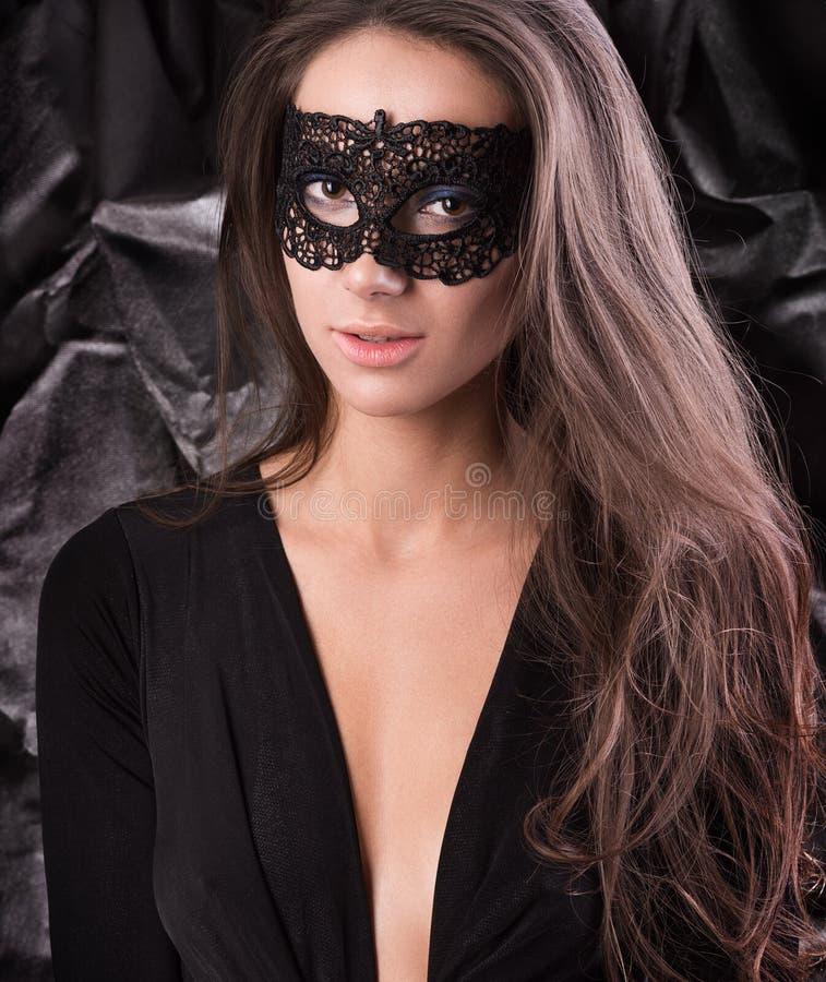 Młoda kobieta w czerni koronki masce na oczach Czarna suknia, luźny włosy fotografia royalty free