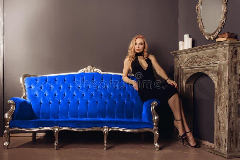 Młoda kobieta w czerni sukni siedzi na błękitnej leżance blisko graby obrazy stock