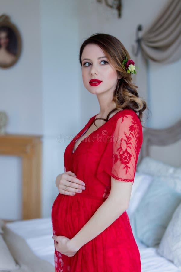 Młoda kobieta w czerwieni sukni pozyci w pokoju fotografia stock