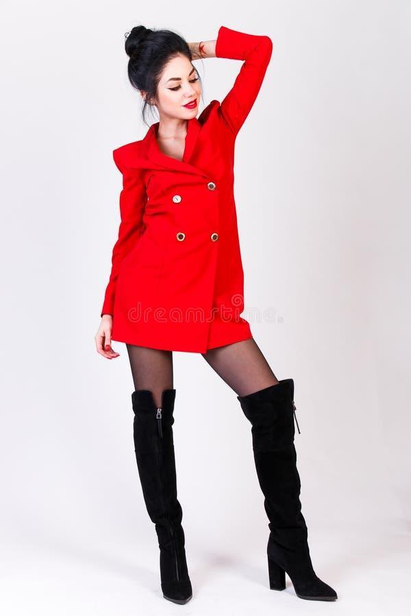 Młoda kobieta w czerwonej kurtce i czerń butach wysoko obraz royalty free