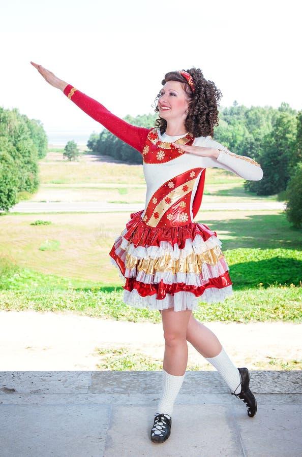 Młoda kobieta w czerwony, biały irlandzki pozować i fotografia royalty free
