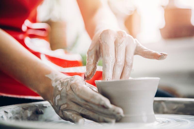 Młoda kobieta w czerwonym fartuchu pracuje za garncarki kołem z długością, robi handmade talerza Poj?cie koncentracja fotografia stock