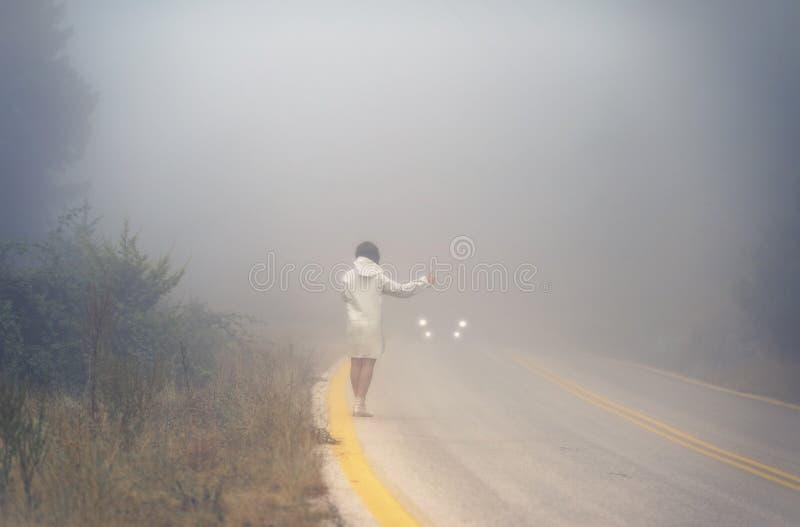 Młoda kobieta w deszczowu na drodze w mgle Podróż kobiety hitchhiking w deszczu w deszczowu zdjęcia stock