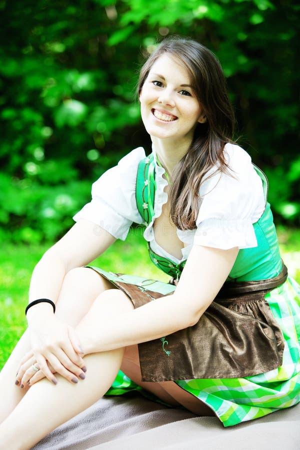 Młoda kobieta w dirndl obsiadaniu na koc w parku obraz stock