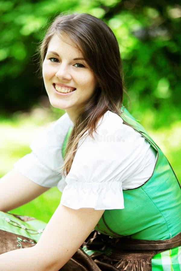 Młoda kobieta w dirndl obsiadaniu na koc w parku fotografia stock