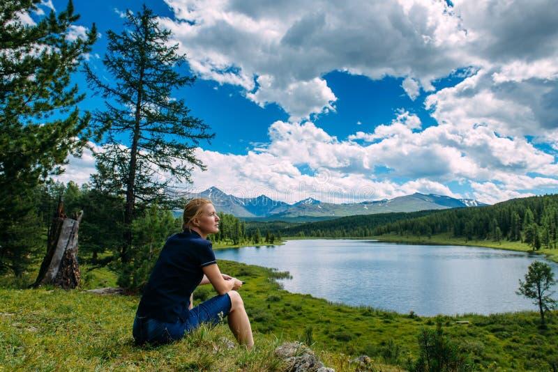Młoda kobieta w drelichowych skrótach siedzi na zielonej trawie, patrzejący w odległość, cieszy się widok obrazy stock