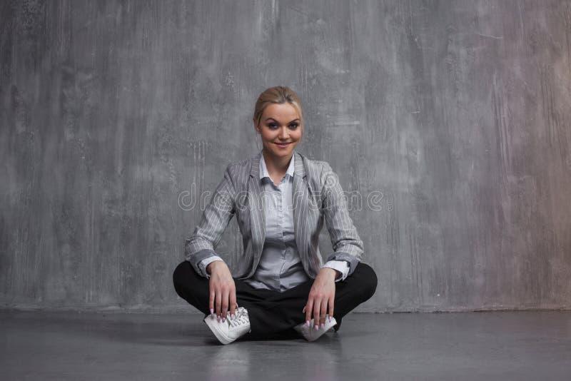 Młoda kobieta w garnituru obsiadaniu w Lotosowej pozie, przywrócić energia, medytuje zdjęcia stock