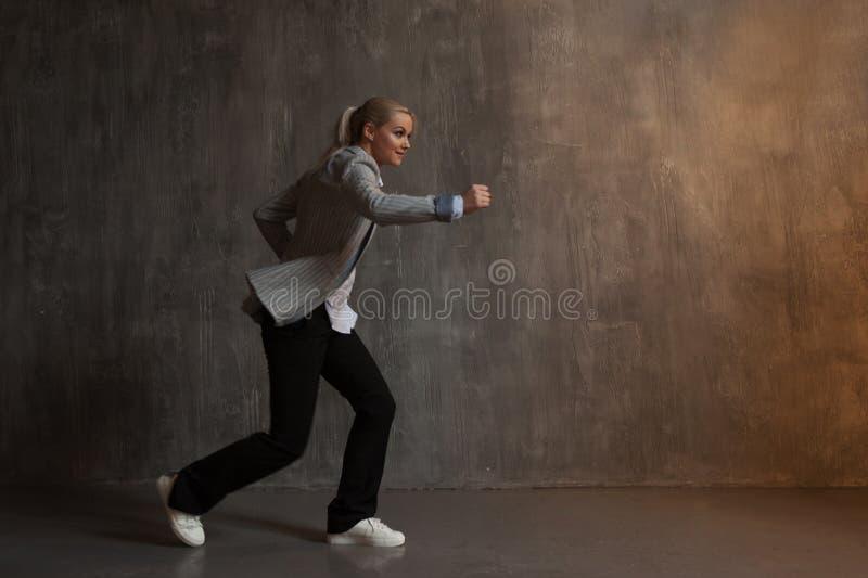 Młoda kobieta w garniturze i sneakers biegacza ` s poza, przygotowywająca biegać długodystansowego fotografia stock