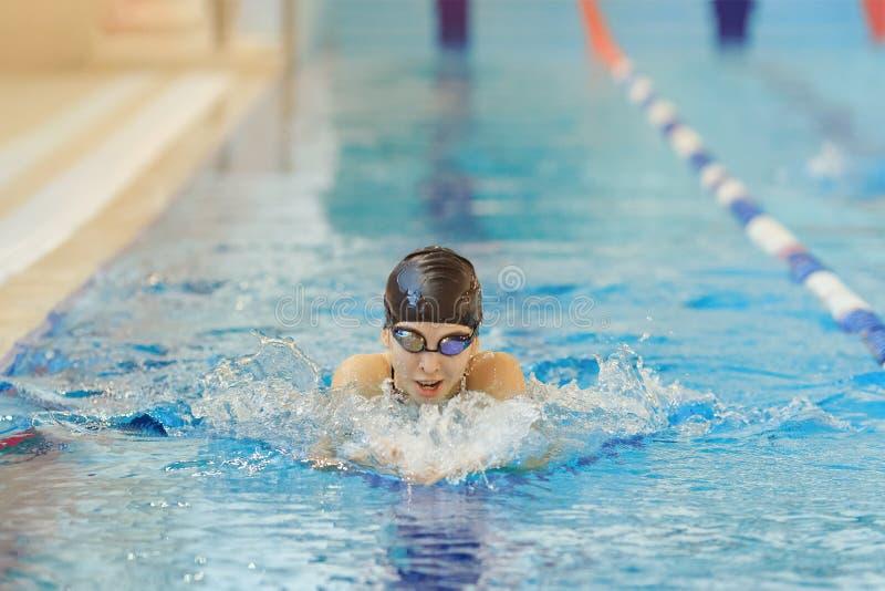 Młoda kobieta w gogle i nakrętki żabki uderzenia pływacki styl w błękitne wody salowym biegowym basenie fotografia stock