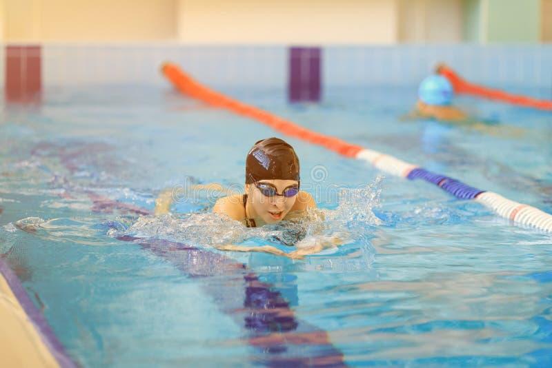 Młoda kobieta w gogle i nakrętki żabki uderzenia pływacki styl w błękitne wody salowym biegowym basenie zdjęcie royalty free