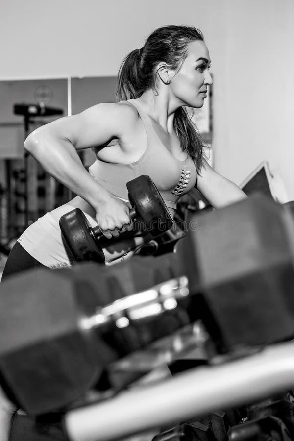 Młoda kobieta w gym udźwigu ciężarach zdjęcia stock