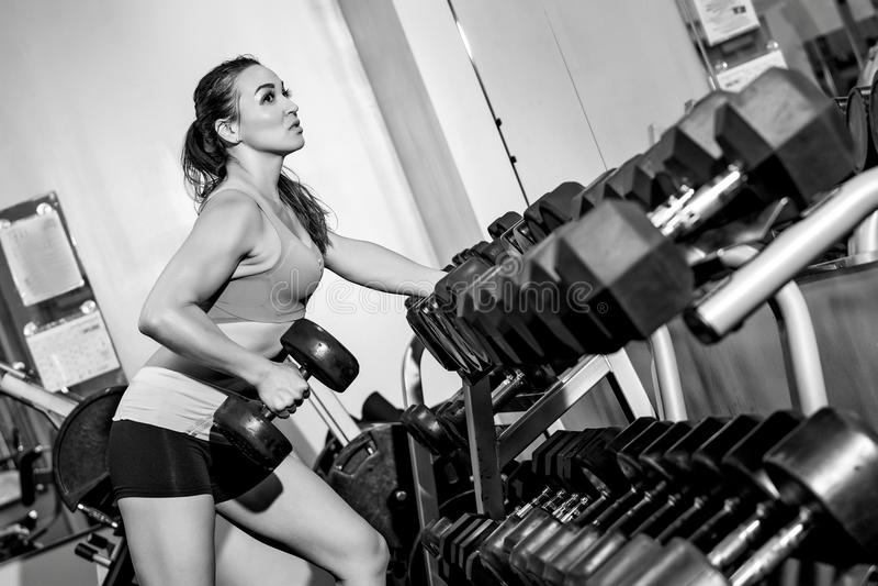 Młoda kobieta w gym udźwigu ciężarach zdjęcie stock