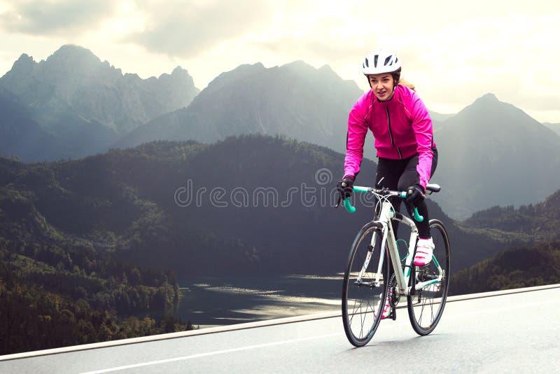 Młoda Kobieta w Jaskrawej Różowej kurtki Jeździeckim Drogowym bicyklu na Halnej Alpejskiej drodze Zdrowy styl życia i przygody po obrazy stock