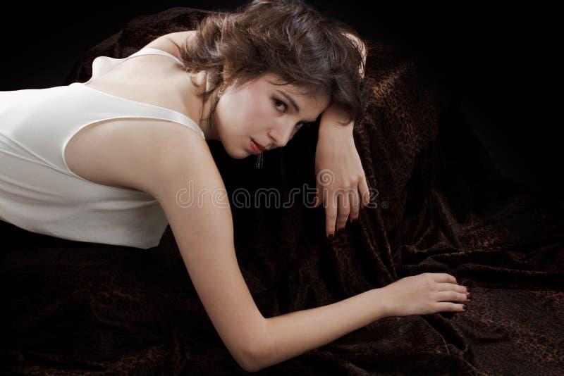 Młoda kobieta w jedwabniczej bluzce opiera na aksamicie obrazy stock