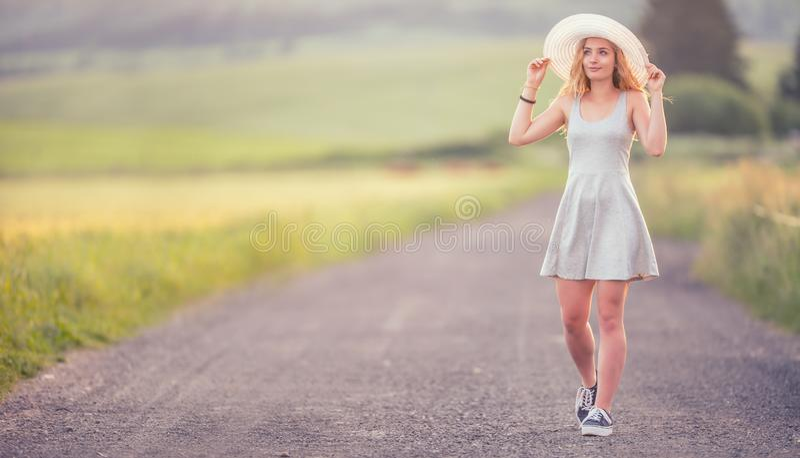Młoda kobieta w kapeluszowym odprowadzeniu na śródpolnej drodze Lato romantyczny wizerunek fotografia royalty free