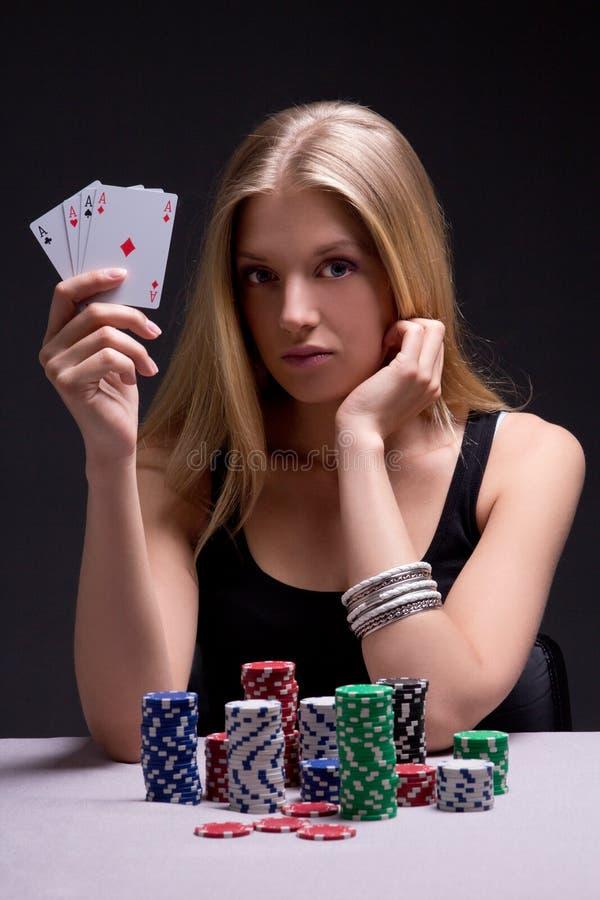 Młoda kobieta w kasynie z kartami i układami scalonymi nad popielatym zdjęcia royalty free