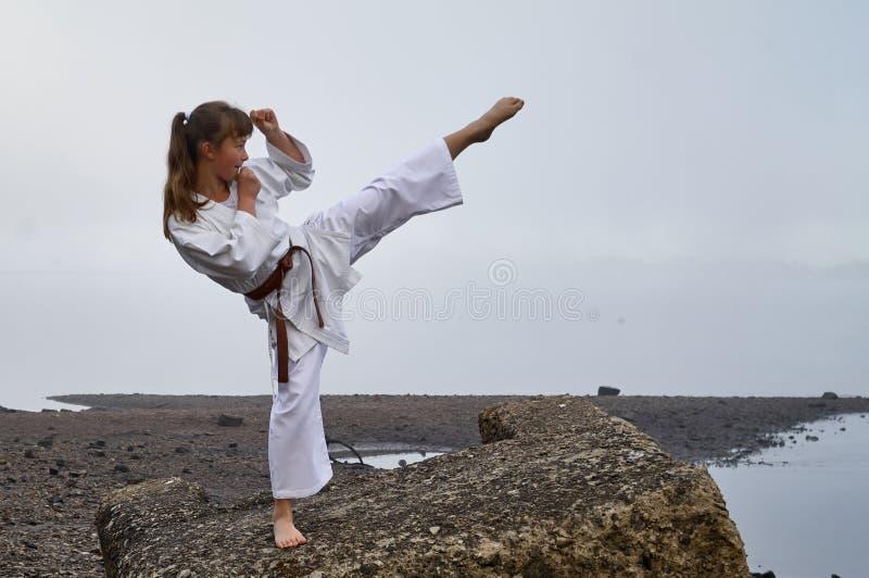 Młoda kobieta w kimono ćwiczy karate zdjęcie royalty free