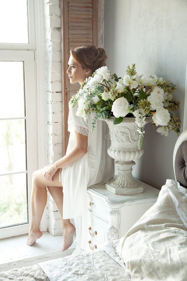 Młoda kobieta w koronkowym bielizny obsiadaniu na łóżkowym gabinecie w luksusie wewnątrz zdjęcie royalty free