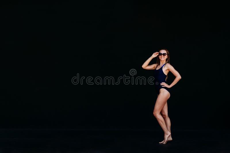 Młoda kobieta w kostiumie sportowym na czarnym tle zdjęcie royalty free