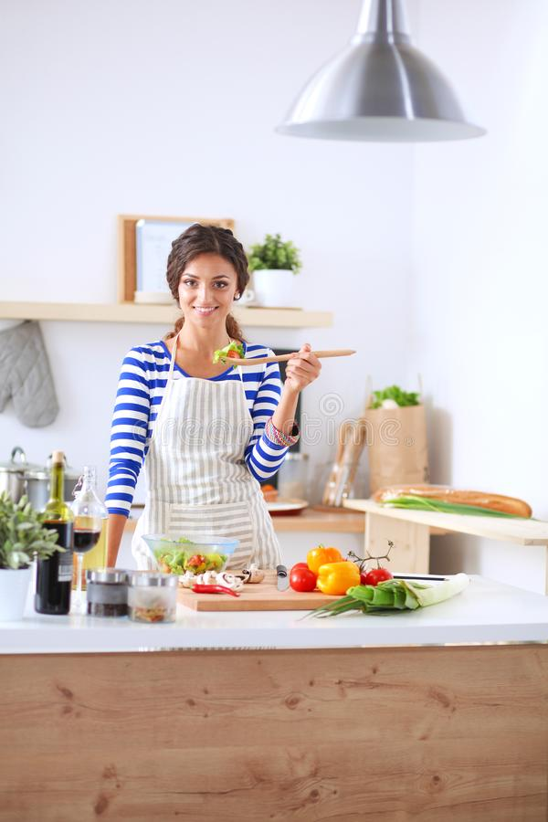 Młoda kobieta w kuchennym narządzaniu jedzenie Młoda kobieta w kuchni obrazy royalty free