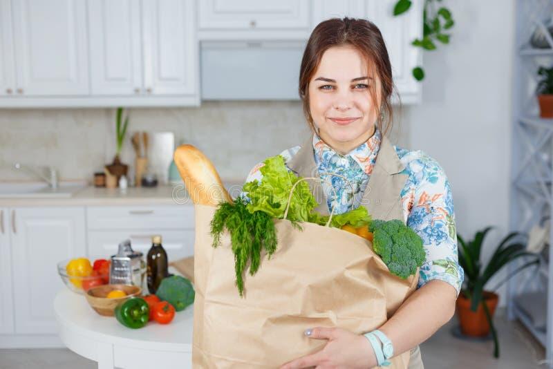 Młoda kobieta w kuchni z torbą sklepu spożywczego zakupy zdjęcia royalty free